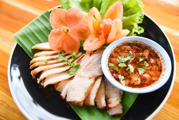 Maiale al forno affettato arrosto di maiale alla griglia con salsa piccante Foto Premium