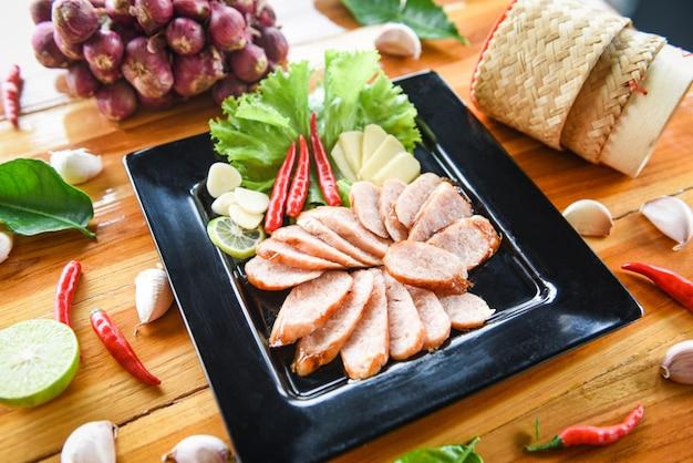 Maiale alla griglia salsicce affettato maiale arrosto con erbe di riso appiccicoso e ingredienti spezie Foto Premium