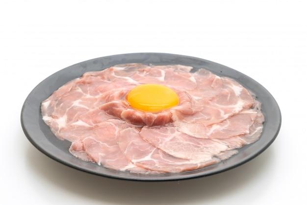 Maiale fresco a fette crudo con uovo per cucinare Foto Premium