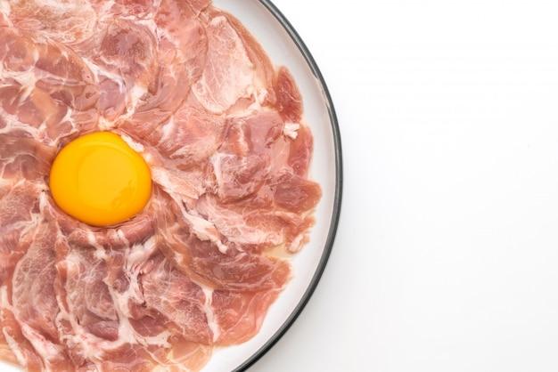 Maiale fresco affettato crudo con uovo per cucinare o fare shabu shabu e sukiyaki Foto Premium