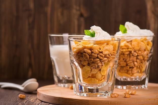 Mais e fiocchi di grano in bicchieri, servito con latte, panna e menta sul tavolo di legno. Foto Premium
