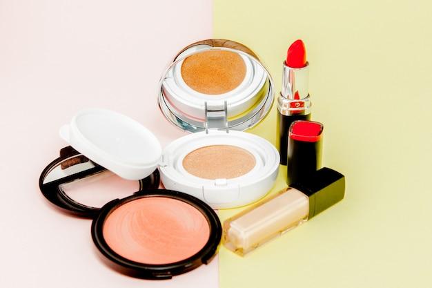 Make up prodotti che si rovesciano su uno sfondo giallo e rosa brillante con spazio di copia Foto Premium