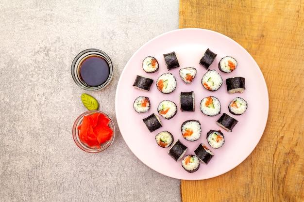 Maki rotola con salsa di zenzero, wasabi e soia sul piatto roseo Foto Premium