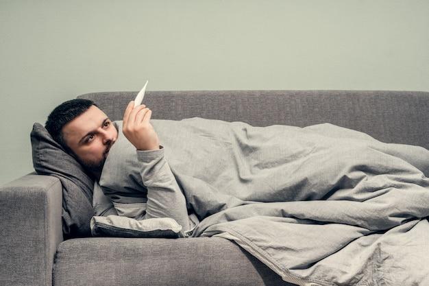 Malattia. esultare a casa. un giovane è malato, viene curato a casa. soffia il naso in un tovagliolo, naso che cola. misurazione della temperatura corporea. infezione, epidemia, portatore di bacillo. coronavirus Foto Premium