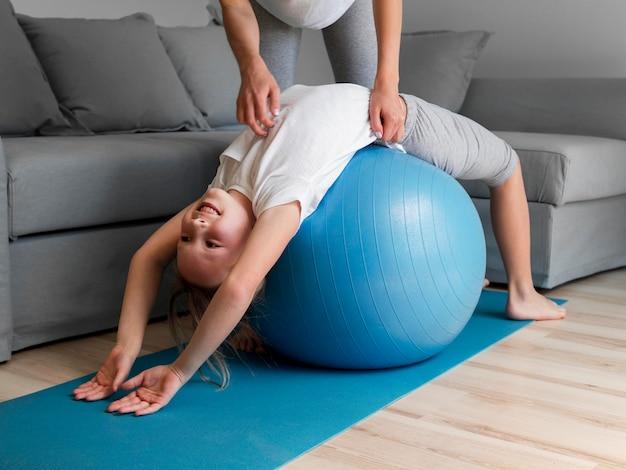 Mamma aiuta la ragazza a esercitarsi sulla palla Foto Gratuite