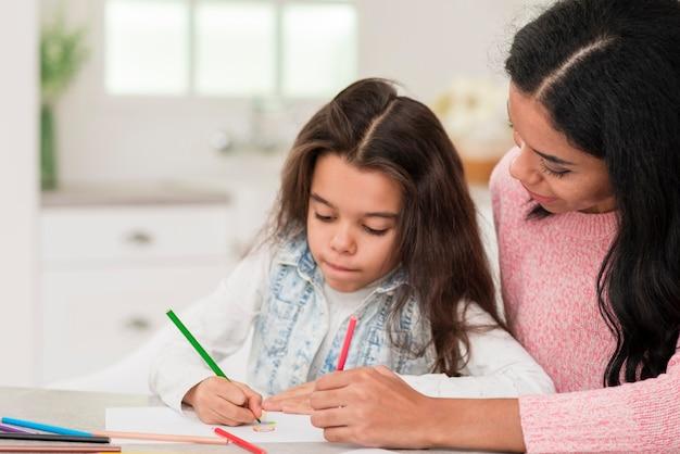 Mamma aiutando la ragazza a colorare il libro Foto Gratuite