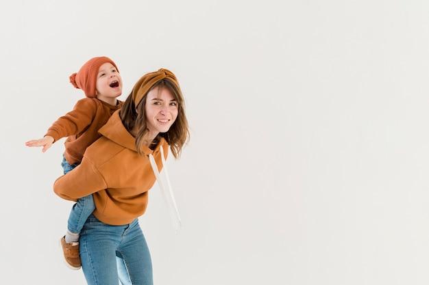 Mamma allegra che offre un giro sulle spalle al figlio Foto Gratuite