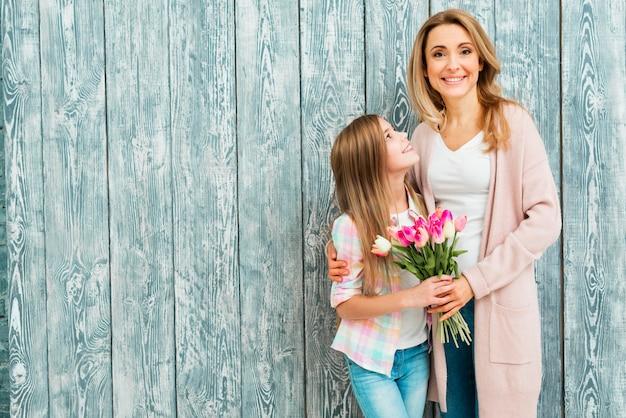 Mamma che abbraccia la figlia e sorridente con i fiori Foto Gratuite