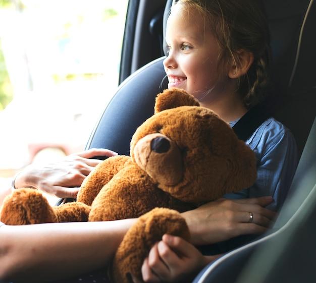 Mamma che aiuta a mettere la cintura di sicurezza Foto Premium
