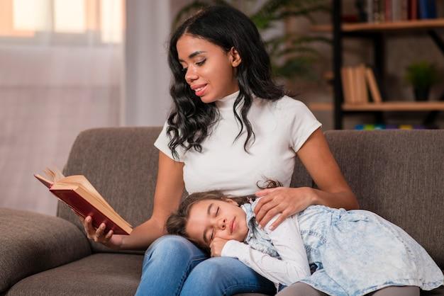 Mamma che legge la storia del letto per la figlia Foto Gratuite