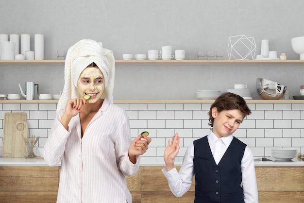 Mamma con maschera e capelli avvolti in un asciugamano che propone una fetta di cetriolo da mangiare a suo figlio Foto Premium