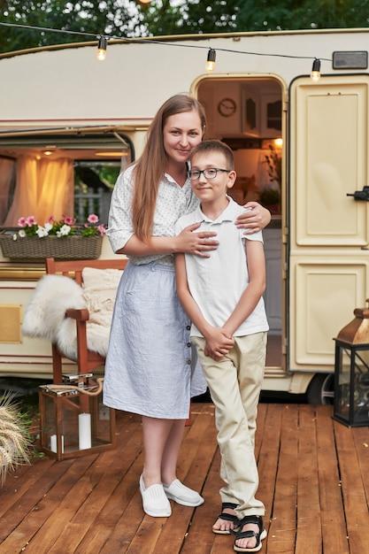 Mamma con suo figlio in vacanza in estate vicino alla casa su ruote Foto Premium
