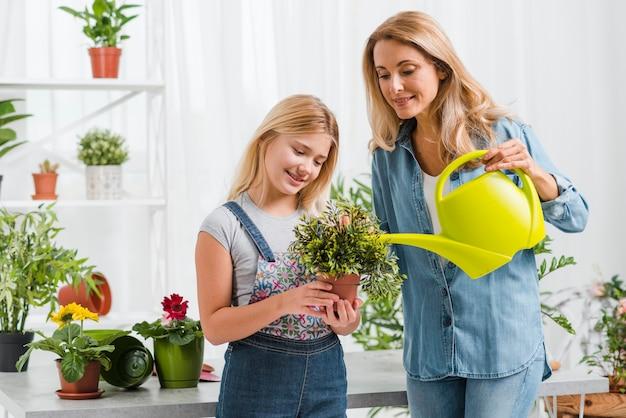 Mamma d'aiuto della ragazza per innaffiare i fiori Foto Gratuite