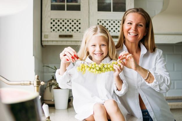 Mamma e figlia bionde felici dei capelli lunghi divertendosi con l'uva in cucina, stile di vita sano della famiglia Foto Premium