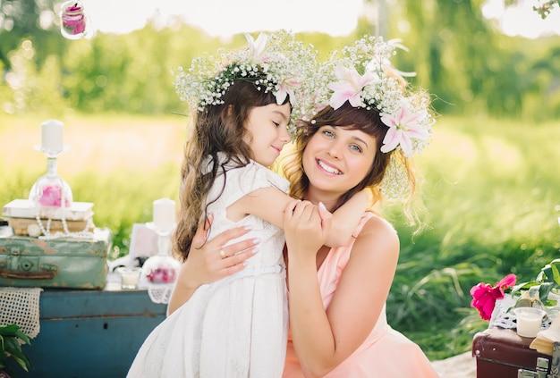 Mamma e figlia che abbracciano su una coperta sull'erba nel parco Foto Premium