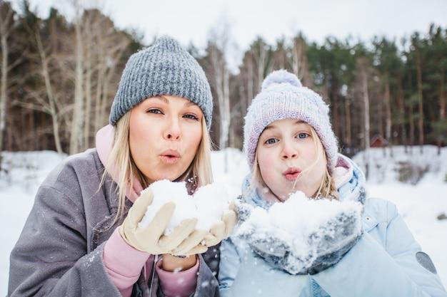 Mamma e figlia che giocano con la neve, soffiando neve dalle loro palme, passeggiata invernale Foto Premium