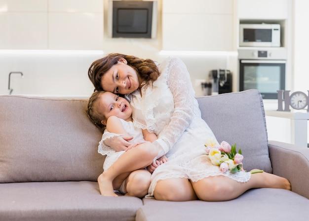 Mamma e figlia divertirsi sul divano a casa Foto Gratuite