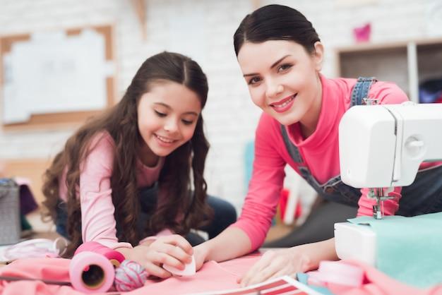 Mamma e figlia piccola cucono insieme i vestiti. Foto Premium