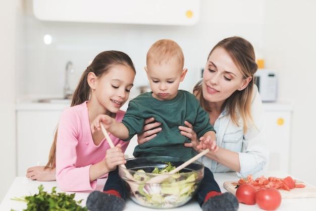 Mamma e figlia si divertono mentre preparano un'insalata Foto Premium