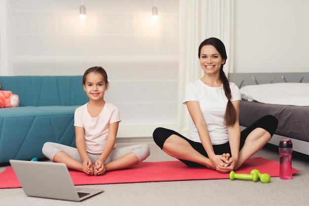 Mamma e figlia stanno facendo ginnastica sul tappeto a casa. Foto Premium