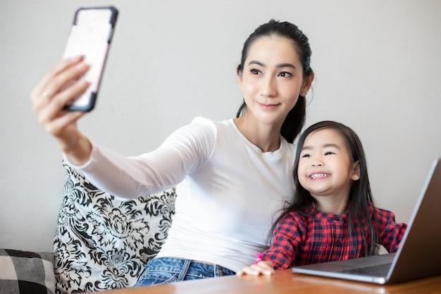 Mamma e figlie stanno prendendo selfie e ridendo e sorridendo felici Foto Premium