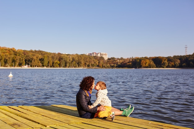 Mamma e figlio che riposano sul lago Foto Gratuite