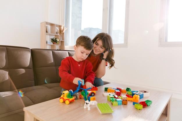Mamma e figlio dell'angolo alto che giocano con i giocattoli Foto Gratuite