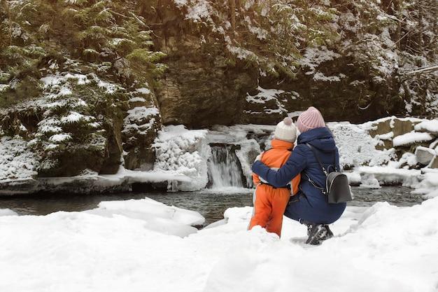 Mamma e figlio seduti in un abbraccio su uno sfondo di neve Foto Premium