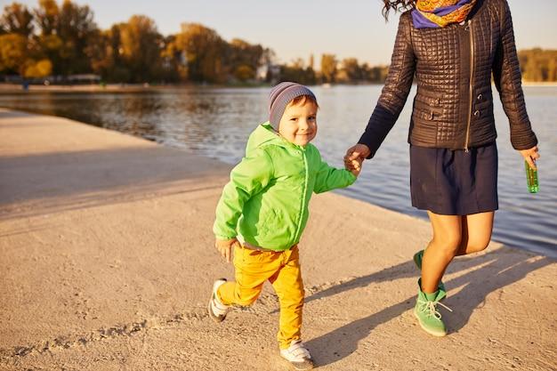 Mamma e figlio si divertono in riva al lago Foto Gratuite