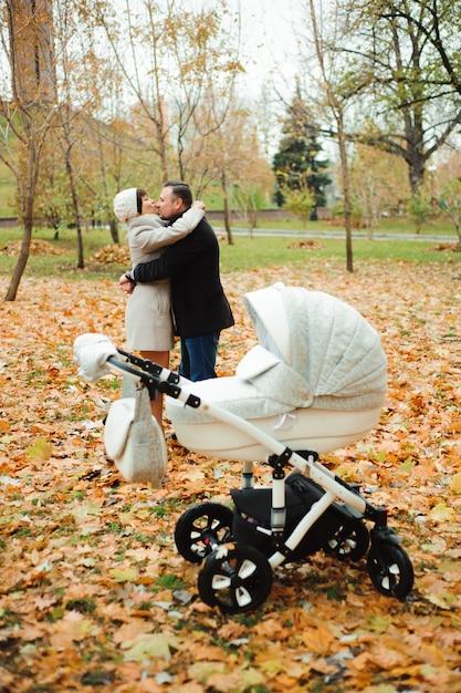 Mamma e papà che abbracciano in un parco in autunno Foto Premium