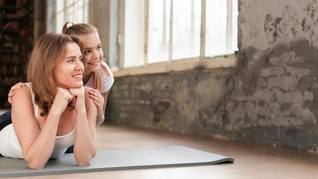 Mamma e ragazza che posano sul distogliere lo sguardo delle stuoie di yoga Foto Gratuite