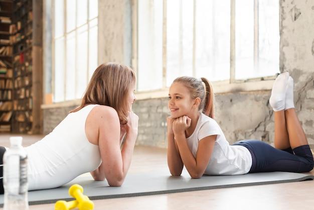 Mamma e ragazza seduta sul tappetino guardando l'altro Foto Gratuite