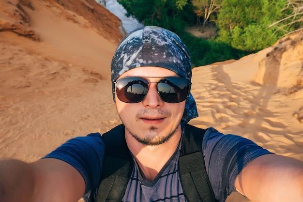 Man hiking fa un selfie sul viso della fotocamera in occhiali da sole e una bandana Foto Premium
