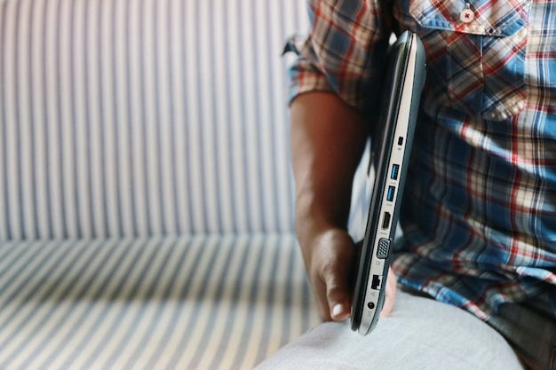 Man hold laptop in braccio e divano copia spazio Foto Premium
