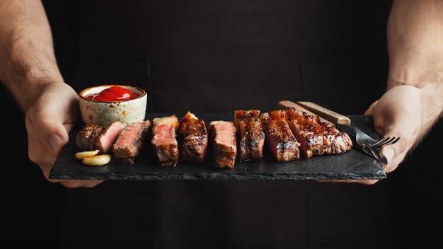 Man holding bistecca di manzo alla griglia succosa. Foto Premium