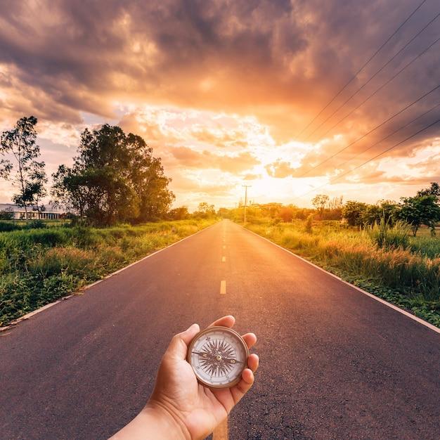Man mano azienda bussola sulla strada con cielo tramonto. Foto Premium