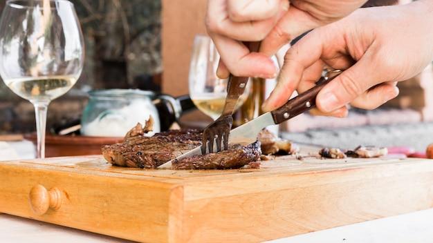 Man mano bistecca di manzo taglio con forchetta e coltello sul tagliere con cassetto Foto Gratuite