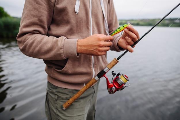 Man mano che impugna il richiamo e la canna da pesca Foto Gratuite