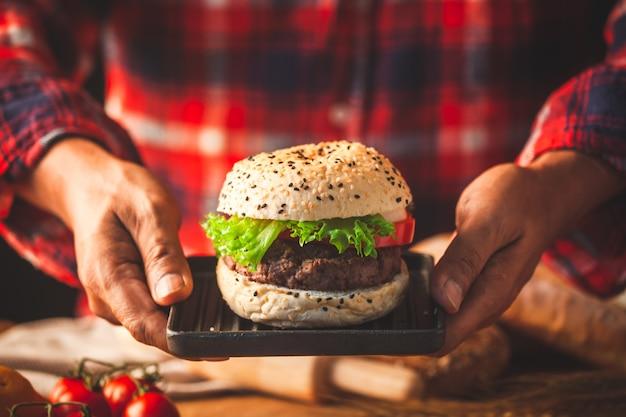 Man mano che tiene delizioso hamburger fatti in casa con verdure fresche, pronti a servire e mangiare Foto Premium