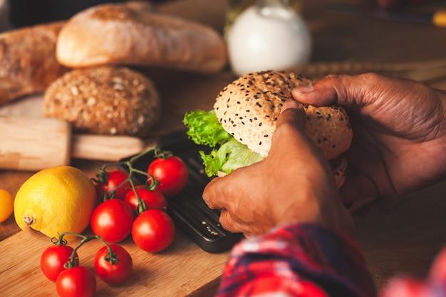 Man mano che tiene delizioso hamburger fatti in casa con verdure fresche Foto Premium