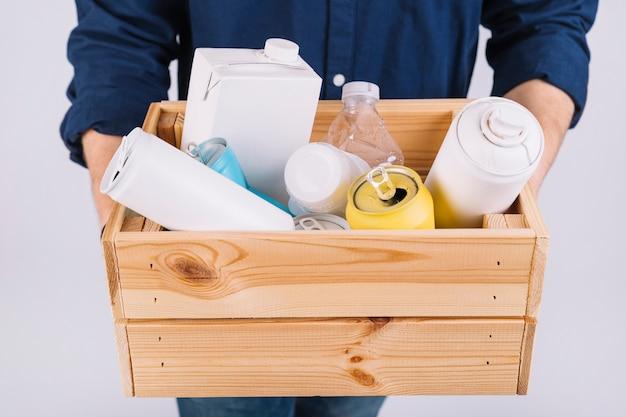 Man mano con scatola di legno piena di bottiglie e lattine Foto Gratuite
