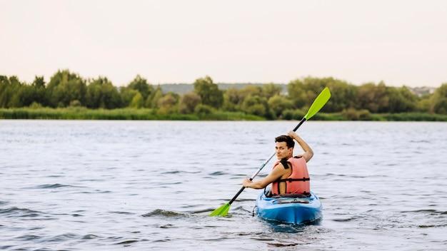Man paddle kayak sul lago guardando indietro Foto Gratuite