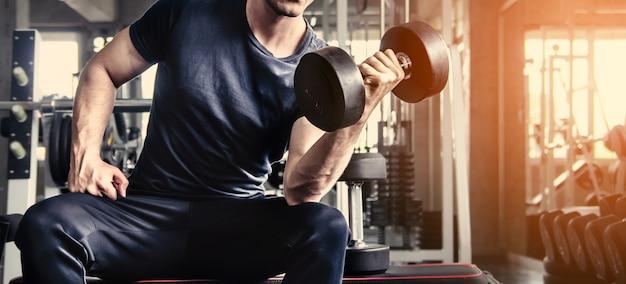 Man pick up dumbell in palestra esercizio con programma di allenamento per la salute Foto Premium