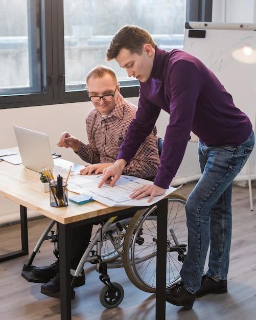 Manager che lavora insieme a un uomo disabile Foto Gratuite
