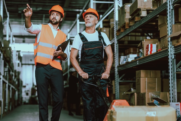 Manager in hardhat talking with warehouse worker Foto Premium