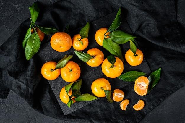Mandarini (arance, mandarini, clementine, agrumi) con foglie. sfondo nero. vista dall'alto Foto Premium