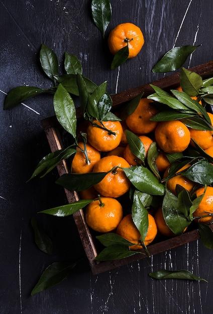 Mandarini con foglie verdi in scatola di legno su oscurità Foto Gratuite