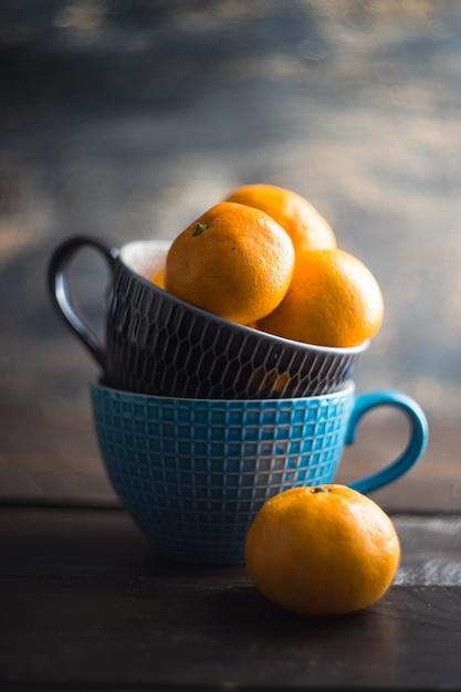 Mandarini organici nella tazza sulla tavola di legno come concetto di inverno Foto Premium