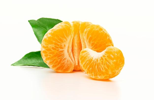 Mandarino isolato. metà del mandarino sbucciato o della frutta arancio con le foglie isolate su fondo bianco. avvicinamento. Foto Premium