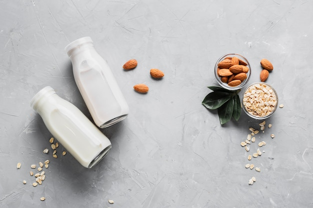 Mandorle piatte e farina d'avena con bottiglie di latte Foto Gratuite